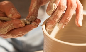 Hands working on pottery wheel , retro style